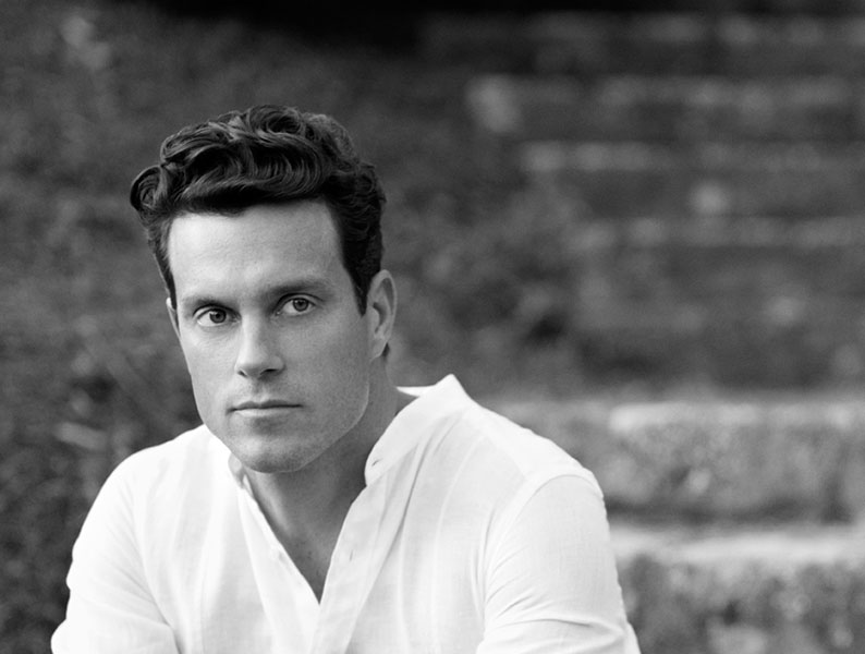 Black and white image of a male model with hair styled by Alpha Male Grooming